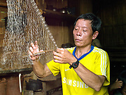 A fisherman makes a fishing net in his home in the Laoseng village of Ban Sopkang, Phongsaly province, Lao PDR. The remote and roadless village of Ban Sopkang is situated along the Nam Ou river (a tributary of the Mekong) and will be relocated due to the construction of the Nam Ou Cascade Hydropower Project Dam 7. The Nam Ou river connects small riverside villages and provides the rural population with food for fishing. But this river and others like it, that are the lifeline of rural communities and local economies are being blocked, diverted and decimated by dams. The Lao government hopes to transform the country into 'the battery of Southeast Asia' by exporting the power to Thailand and Vietnam.