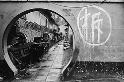 "circular door and painted sign saying ""demolish""  in a hutong in Beijing"
