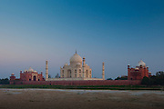 The Taj Mahal and Mosque North Side viewed across Yamuna River at sunset , India