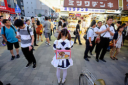 Young woman advertising Maids' Cafe in Akihabara known as Electric Town or Geek Town selling Manga based games and videos in Tokyo Japan