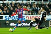 Wilfried Zaha (#11) of Crystal Palace hits a shot on goal as Federico Fernandez (#18) of Newcastle United attempts to make a block during the Premier League match between Newcastle United and Crystal Palace at St. James's Park, Newcastle, England on 21 December 2019.