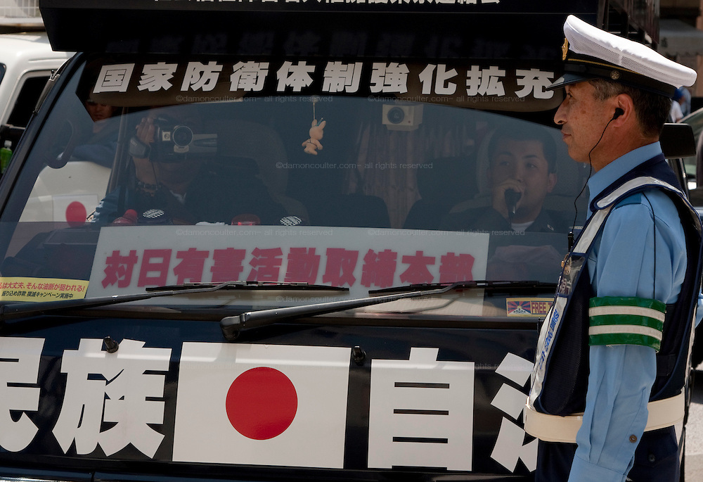 A sound truck from the paramilitary right wing Uyoku Dantai is prevented from going through a road block by a policeman outside Yasukuni Shrine. On August 15th every year people gather at Yasukuni Shrine to commemorate the end of the Pacific War. Notionally a call for remembrance and continued peace it is also a Mecca for right wing nationalist including  the paramilitary Uyoku Dantai. Tokyo, Japan, August 15th 2009