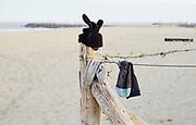 Aan het begin van het strand hangen gevonden voorwerpen aan een hek met prikkeldraad. | At the beginning of the beach, found objects hang from a barbed wire fence.