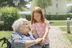 Senior woman on wheelchair with granddaughter, Bavaria, Germany