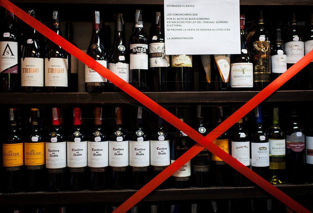 Bottles of wine in a supermarket of La Paz. Alcohol is forbidden for sale 48 hours before and 12 after Election Day according to the law by the Electoral Tribunal. During elections period in  Bolivia, the country faces several restrictions, like no alcohol for sale 48 hours before and 12 after the election; no public gatherings, shows of any kind until the political parties made their speeches on the election night; its completely forbidden the circulation of any vehicles, private or governmental except with the permit from the Electoral Tribunal, which means it would be basically no cars, buses or anything circulating in the city; no long distance buses, the terminal will be close from Saturday until Monday and even flights will not be allowed except the ones leaving the country or the international ones doing stop-over. It is a completely shut down of the country.