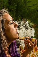 Young woman smoking marijuana in a pipe, LIttleton, Colorado USA.