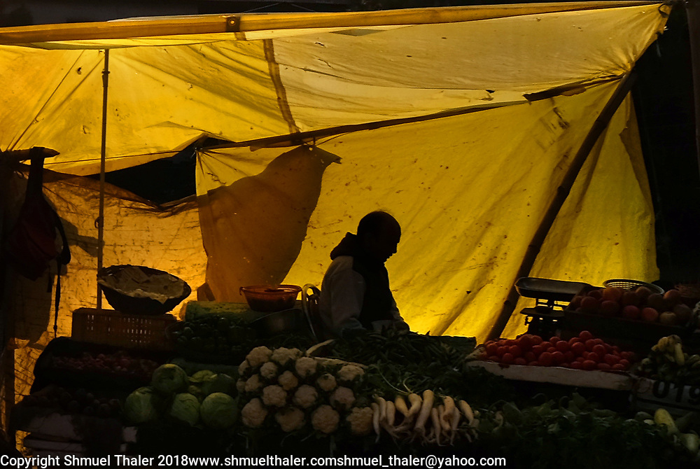 Produce seller silhouetted along the road near Dharmshala, India.<br /> Photo by Shmuel Thaler <br /> shmuel_thaler@yahoo.com www.shmuelthaler.com