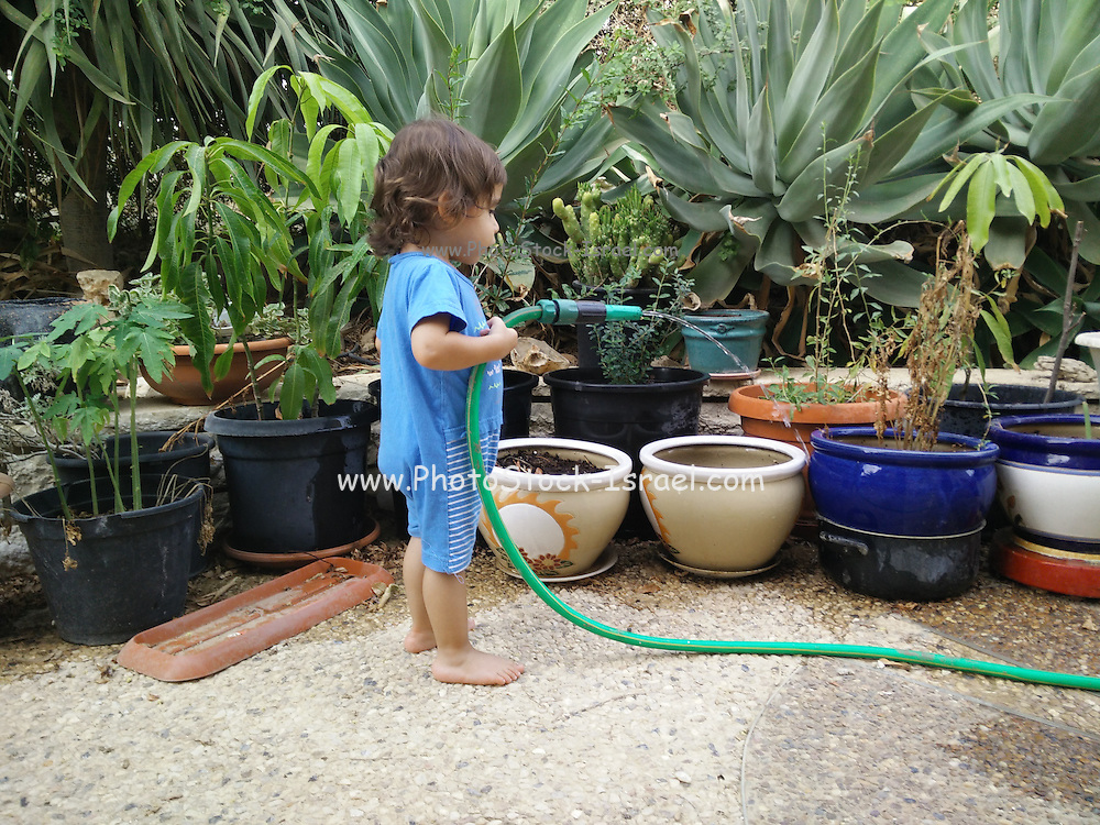 Young girl watering pot plants