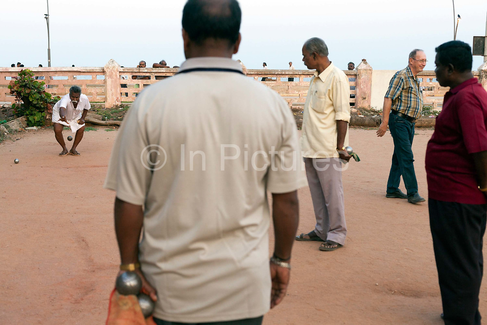 Men play a game of Pétanque on some waste ground near the beach, Pondicherry, India. A French tourist has just thrown. Pondicherry now Puducherry is a Union Territory of India and was a French territory until 1954 legally on 16 August 1962. The French Quarter of the town retains a strong French influence in terms of architecture and culture.