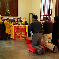 Asia, China, Shanghai. Monks actviely worship at the Jade Buddha Temple.