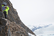 Shad O'Neel, glaciologist with the USGS, climbs a cliff to service an Extreme Ice Survey timelapse camera overlooking the Columbia Glacier, near Valdez, Alaska.