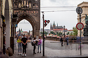 "Mostly Czech citizens waiting at a traffic light in the beginning of Charles Bridge leading towards ""Lesser Town"" (Mala Strana) and Prague Castle which is normally a highly frequented crossing during the tourist season. The Czech government lowered the security measures and as of Monday 25 May 2020, wearing of protective masks will be mandatory only in the interiors of buildings other than the place of residence and in public transport."