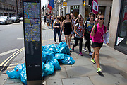 Summertime in London, England, UK. Rubbish recycling bags left on the street in Mayfair. Collection of recyclable waste is the city is important business, while doesn't always make the streets look clean.