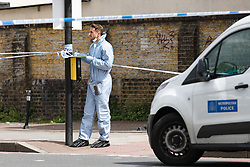 © Licensed to London News Pictures. 08/08/2017. LONDON, UK.  A forensic officer at the crime scene cordon on the corner of Old Kent Road and Ilderton Road, next to the Afrikiko Bar Restaurant and Club. Police were called at around 2am and found a 19 year old man with stab injuries, who was pronounced dead about an hour later. Five people have now been arrested in connection with stabbing and are being held at a south London police station.  Photo credit: Vickie Flores/LNP