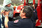 Firefighter age 45 and baby at Cinco de Mayo festival.  St Paul Minnesota USA
