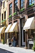 Shoppers at traditional antique shop with awnings on Belgian shopping street in Bruges,  Belgium
