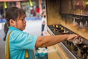 27 NOVEMBER 2012 - BANGKOK THAILAND:  A woman makes merit by pouring lamp oil into lamps at Wat Sri Boonreung on Klong Saen Saeb in Bangkok, Thailand.       PHOTO BY JACK KURTZ