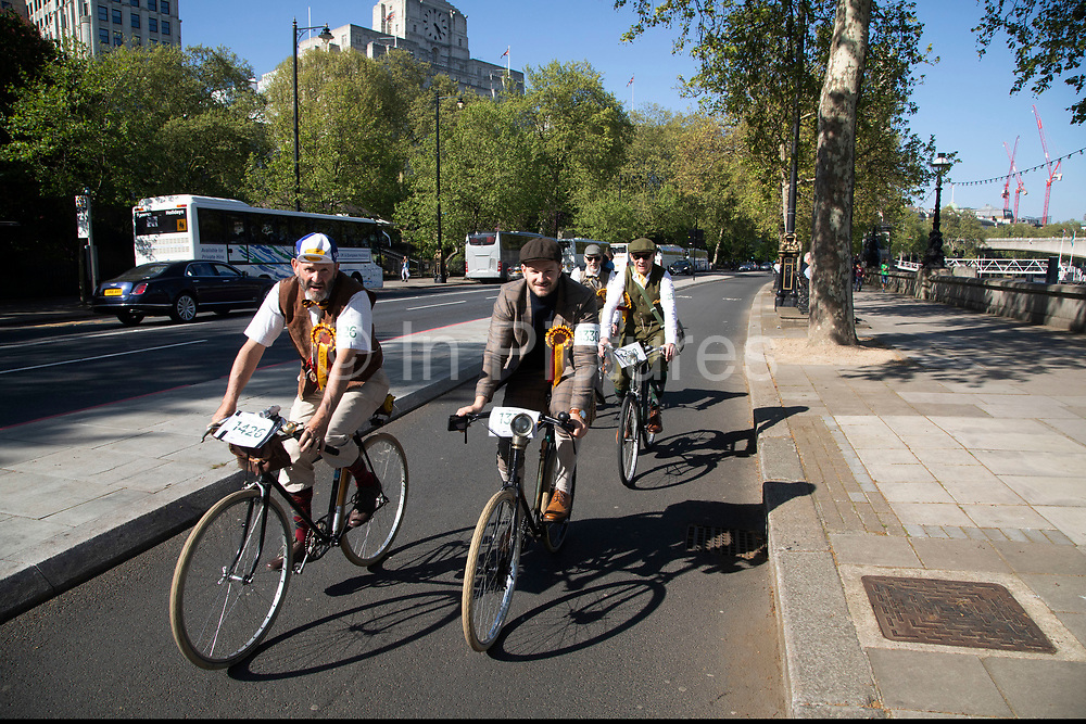 Tweed Run participants cycling along a cycle superhighway after their vintage day out in London, United Kingdom. The Tweed Run is a group bicycle ride through the centre of London, in which participants dress in traditional British attire, particularly tweed plus four suits.