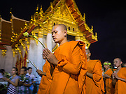 """04 MARCH 2015 - BANGKOK, THAILAND: Buddhist monks participate in a procession around the """"wiharn,"""" or prayer hall, at Wat Benchamabophit on Makha Bucha Day. Makha Bucha Day is an important Buddhist holy day and public holiday in Thailand, Cambodia, Laos, and Myanmar. Many people go to temples to perform merit-making activities on Makha Bucha Day. Wat Benchamabophit is one of the most popular Buddhist temples in Bangkok.    PHOTO BY JACK KURTZ"""