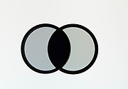 Two polarizing filters shown at a 90-degree angle to each other.  In this orientation, the crossed filters block over 99% of the transmitted light.
