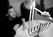 A Jewish family celebrates Hanukkah at home by lighting the candles of a menorah.