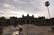 A woman clears puddles of water from the front of Angkor Wat in Cambodia