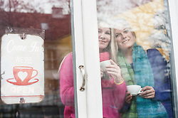 Two friends looking through window and drinking coffee in coffee shop, Bavaria, Germany