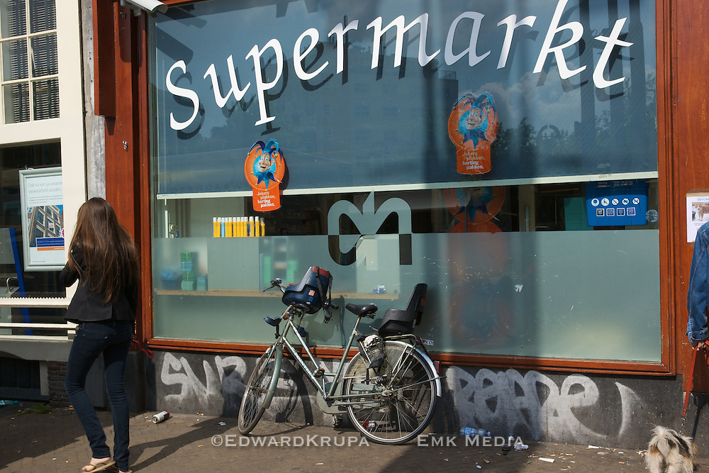 A woman on a mobile phone walks by a Supermarket in Amsterdam.