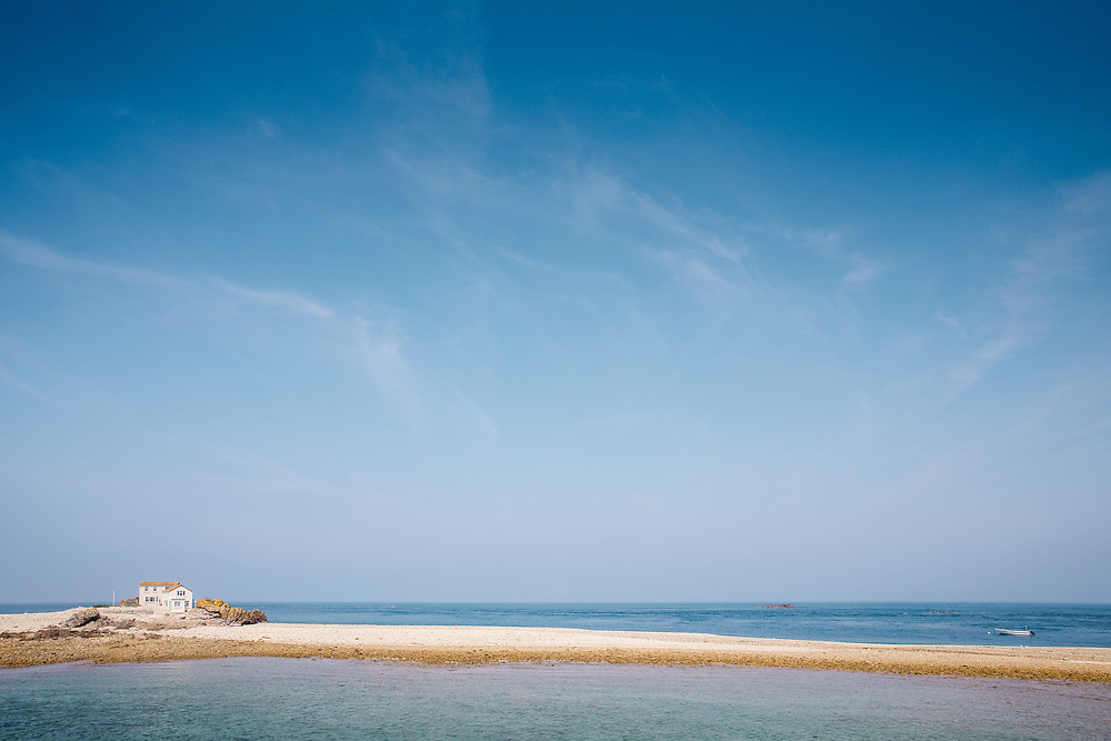 A deserted beach surrounded by calm blue sea at the popular tourist attraction, the Ecrehous, off the coast of Jersey, Channel Islands
