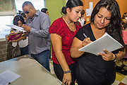"""18 AUGUST 2012 - PHOENIX, AZ:  People sign into the deferred action workshop at Neighborhood Ministries in Phoenix. More than 1000 people attended a series of 90 minute workshops in Phoenix Saturday on the """"deferred action"""" announced by President Obama in June. Under the plan, young people brought to the US without papers, would under certain circumstances, not be subject to deportation. The plan mirrors some aspects the DREAM Act (acronym for Development, Relief, and Education for Alien Minors), that immigration advocates have sought for years. The workshops were sponsored by No DREAM Deferred Coalition. PHOTO BY JACK KURTZ"""