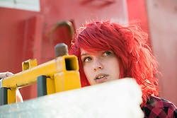 Young teenage girl dyed red hair piercings