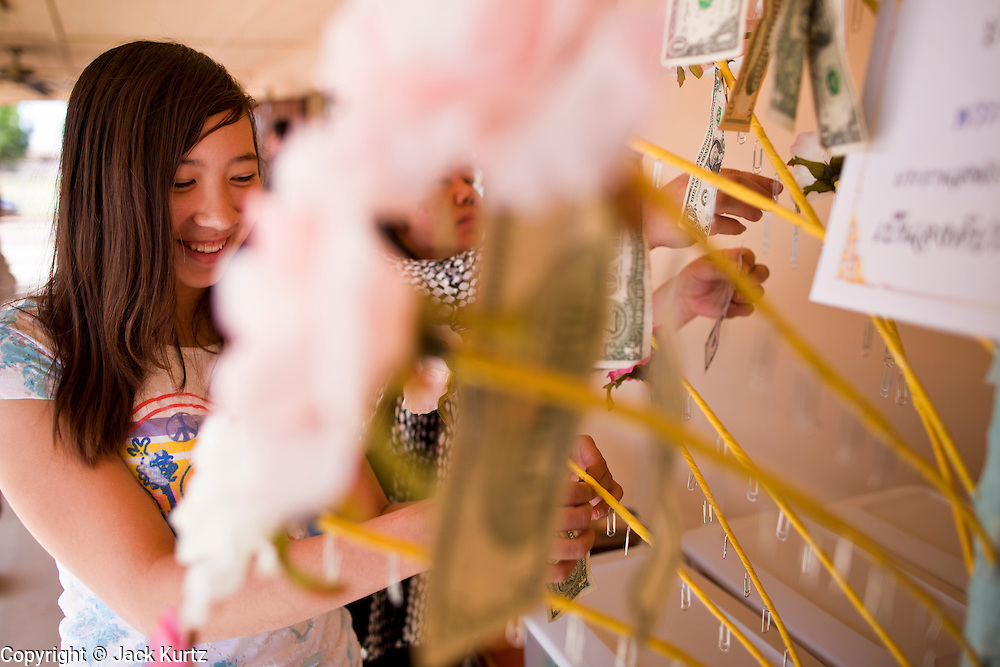 24 OCTOBER 2010 - CHANDLER, AZ: A woman makes a financial contribution to the temple during the Ok Phansa services to mark the end of Buddhist Lent at Wat Pa, in Chandler, AZ, Sunday October 24. Buddhist Lent is a time devoted to study and meditation. Buddhist monks remain within the temple grounds and do not venture out for a period of three months starting from the first day of the waning moon of the eighth lunar month (in July) to the fifteenth day of the waxing moon of the eleventh lunar month (in October). Ok Phansa Day marks the end of the Buddhist lent and falls on the full moon of the eleventh lunar month, this year Oct 23. Wat Pa, a Thai Theravada Buddhist temple, celebrated Ok Phansa Day on October 24.    Photo by Jack Kurtz