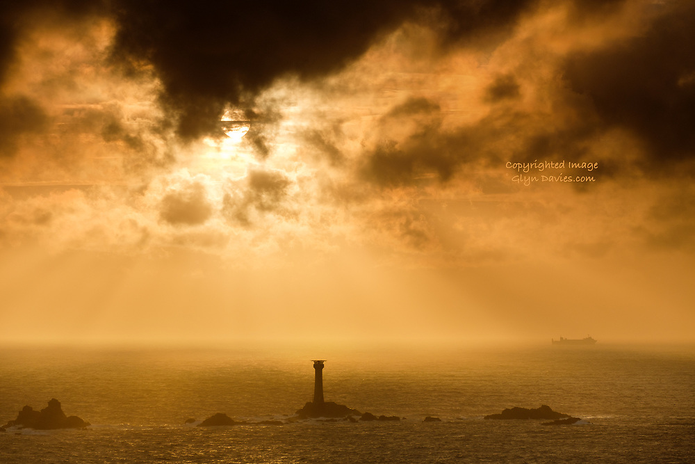 A small cargo ship passes by Longships Lighthouse just off the coast at Land's End, SW Cornwall during an amazing and dramatic sunset. No filters, just incredible colour saturated light from the sun burning through layers of cloud and vapour.