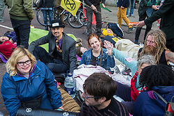 London, UK. 9 October, 2019. Climate activists from Extinction Rebellion use lock-on arm tubes and glue to block Birdcage Walk on the third day of International Rebellion protests to demand a government declaration of a climate and ecological emergency, a commitment to halting biodiversity loss and net zero carbon emissions by 2025 and for the government to create and be led by the decisions of a Citizens' Assembly on climate and ecological justice.