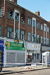 © Licensed to London News Pictures.  10/07/2013. LONDON, UK. A phone box (bottom right), with a damaged roof. The damage is believed to be from a person jumping from a second storey window attempting to escape a fire in flat above a shop on New Heston Road (Church Road), Hounslow. Two men and a woman jumped from the building before fire crews arrived. The woman, thought to be 30 years old, died at the scene and another body was discovered inside. Photo credit: Cliff Hide/LNP