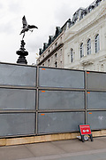 "A two direction sign for pedestrians leans against a temporary construction hoarding, beneath the partially hidden statue of the world famous London Victorian-era landmark, Eros in Piccadilly Circus, on 25th February 2020, in London, England. Eros, or the Shaftesbury Memorial Fountain is located at the southeastern side of Piccadilly Circus in London, United Kingdom. Moved after World War II from its original position in the centre, it was erected in 1892–1893 to commemorate the philanthropic works of Lord Shaftesbury, who was a famous Victorian politician and philanthropist. The monument is surmounted by Alfred Gilbert's winged nude statue generally, though mistakenly, known as Eros. This has been called ""London's most famous work of sculpture."""