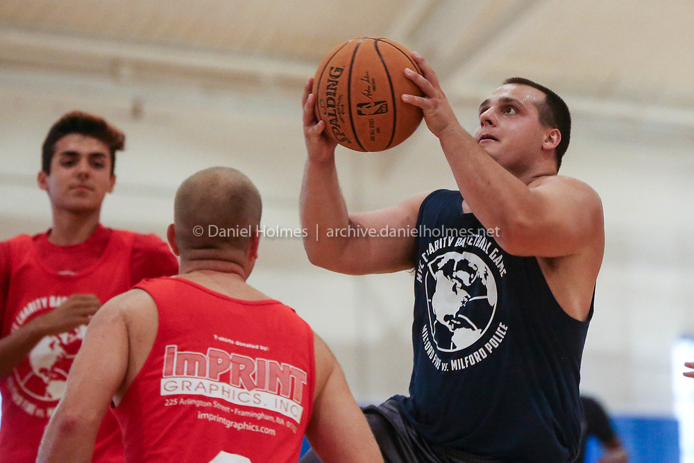 (9/15/18, MILFORD, MA) Milford officer Elias Giokas goes up for the layup during the youth center fundraising basketball game at the Milford Youth Center on Saturday. [Daily News and Wicked Local Photo/Dan Holmes]