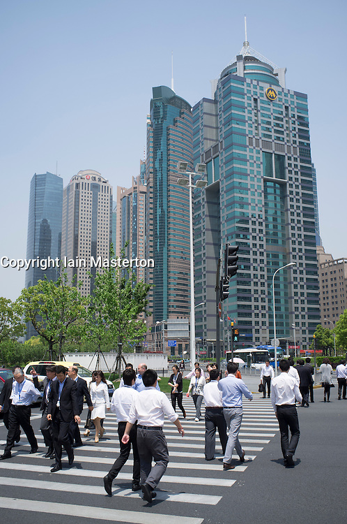 Office workers crossing street in financial district at Lujiazui Pudong in Shanghai China