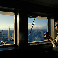 USA, Alaska, Second mate keeps watch on bridge of oil tanker sailing at sunset