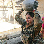 A member of the Female Engagement Team (FET) gathering water from a gutter for the water demonstration  in the village of Nari, Kunar Province of Eastern Afghanistan.