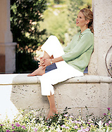 This picture was photographed for a clothing catalog; our model Jane is sitting on a coral wall, admiring  the beautiful garden.