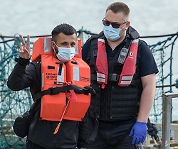 © Licensed to London News Pictures. 03/08/2021. Dover, UK. A  migrant gestures as he is helped ashore by a Border Force officer at Dover Harbour in Kent after crossing the English Channel. Hundreds of migrants have made the crossing in recent weeks. Photo credit: Stuart Brock/LNP