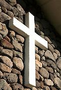 A white cross on a stone wall on Molokai.