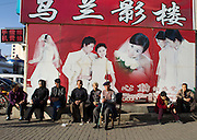A group of elderly people sit next to a sign advertising wedding photos in Hohhot.