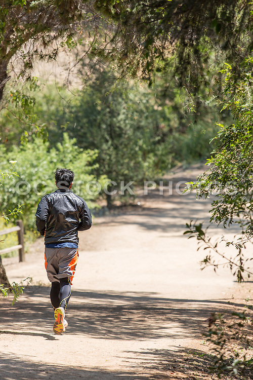 Man Jogging on Trail at Ralph B. Clark Regional Park in Buena Park
