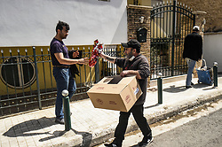 Konstantinos Polychronopoulos (R) distributes meals to migrants, outside the premises of the social kitchen 'The other human' in Athens, Greece, on 15 April 2020. - The social kitchen appeared in the middle of the Greek financial crisis, adapting now during the COVID-19 pandemic and confinement, distributing meals to unemployed, migrants, homeless and elderly people.<br />