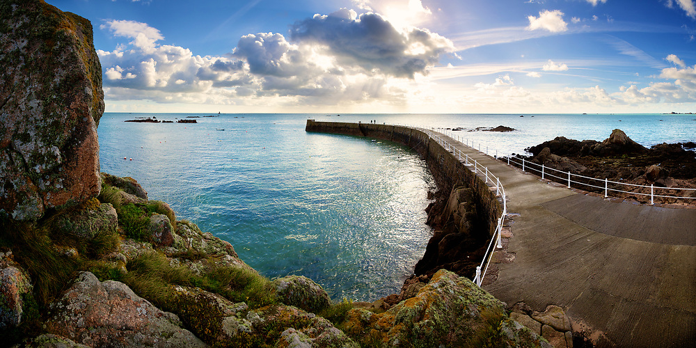 The causeway, pier and water surrounding it at La Rocque at high tide on a sunny day along the east coast of Jersey