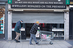 © Licensed to London News Pictures 05/02/2021.        Bexleyheath, UK. Shoppers out and about walking past a closed jewellers on The Broadway in Bexleyheath, South East London today as the R-rate drops below 1 in England for the first time since July last year. Photo credit:Grant Falvey/LNP