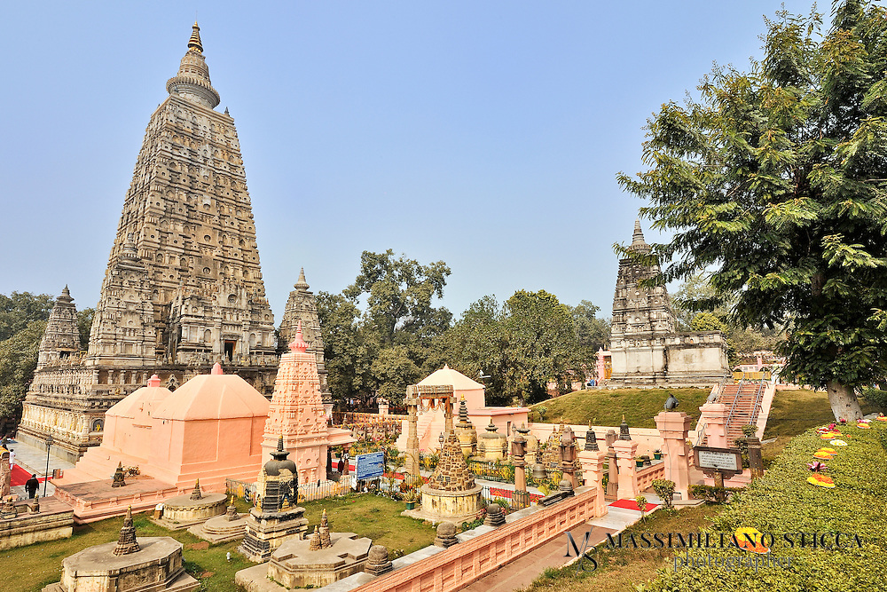 """The historical place at which the Enlightenment took place became a place of pilgrimage. Though it is not mentioned in the scriptures, the Buddha must have visited Bodh Gaya again in the course of his teaching career. About 250 years after the Enlightenment, the Buddhist Emperor, Ashoka visited the site and is considered the founder of the Mahabodhi Temple. According to the tradition, Ashoka, as well as establishing a monastery, erected a diamond throne shrine at this spot with a canopy supported by four pillars over a stone representation of the Vajrasana, the Seat of Enlightenment.<br /> The temple's architecture is superb but its history is shrouded in obscurity. It was constructed with the main intention of making it a monument and not a receptacle for the relics of the Buddha. Several shrines were constructed with enshrined images for use as places of worship.<br /> The basement of the present temple is 15m square, 15m in length as well as in breadth and its height is 52m which rises in the form of a slender pyramid tapering off from a square platform. On its four corners four towers gracefully rise to some height. The whole architectural plan gives pose and balance to the observers.<br /> Inside the temple there is a colossal image of the Buddha in the """"touching the ground pose"""", bhumisparsha mudra. This image is said to be 1700 years old and is facing east exactly at the place where the Buddha in meditation with his back to the Bodhi tree was enlightened."""