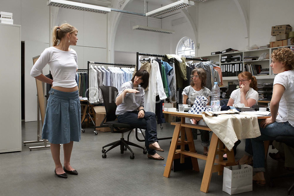 """An employee of British couturier Margaret Howell models a simple white top in the company's retail flagship and design studio at 34 Wigmore Street, Central London England. In a back rooom studio workshop, the group of 5 staff with Margaret Howell in the middle, they dicsuss the positives of the garment that is considered for a forthcoming collection. Racks of clothes are in the background and they sit around a trestle table. Howell is one of Britain's more understated of couture brands alongside more flamboyant personalities. Howell admits to being """"inspired by the methods by which something is made .. enjoying the tactile quality of natural fabrics such as tweeds, linen and cotton in a relaxed, natural and lived in look."""""""